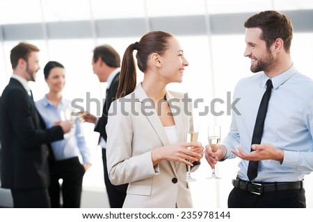 Celebrating their common success. Two cheerful business people drinking champagne and talking while other people communicating in the background  - stock photo