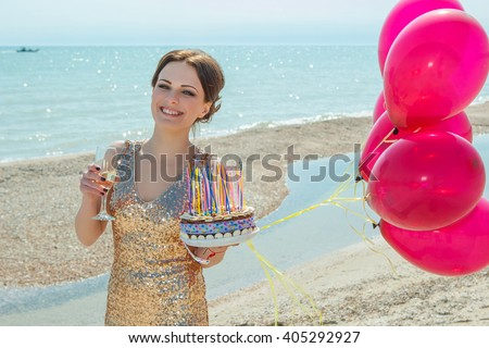 celebration and lifestyle concept - beautiful happy woman in gold dress with red balloons, glass champagne, cake on the sea