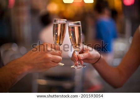 Celebration: cheering with a glass of champagne - stock photo