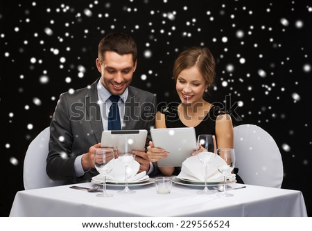 celebration, christmas, holidays, technology and people concept - smiling couple with tablet pc computers at restaurant over black snowy background - stock photo