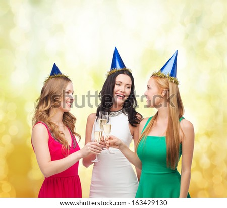 celebration, drinks, friends, bachelorette party, birthday concept - three smiling women wearing blue hats with champagne glasses