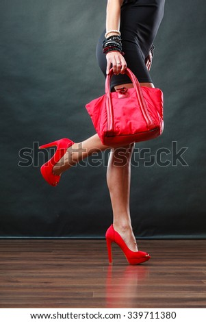 Celebration evening fashion concept. Woman in black short dress red spiked shoes holding handbag bag, female legs in high heels on party floor - stock photo