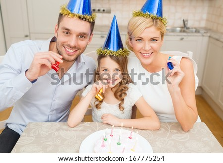 celebration, family, holidays and birthday concept - happy family in blue hats with cake and candles blowing favor horns - stock photo