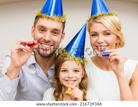celebration, family, holidays and birthday concept - three smiling women wearing blue hats and blowing favor horns - stock photo