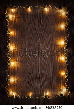 celebration garland of light bulbs on wooden background copy space for inscriptions - stock photo