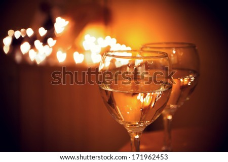Celebration.Glasses of wine. The concept of Valentine's Day. Bokeh in the background of glasses are shaped like heart.