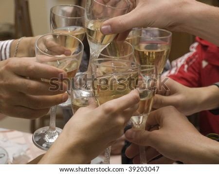 Celebration. Hands holding the glasses of champagne making  a toast. - stock photo