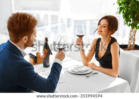 Celebration. Happy Romantic Couple In Love Cheering With Glasses Of Red Wine, Having Dinner In Luxury Gourmet Restaurant, Celebrating Anniversary Or Valentine's Day. Romance, Relationship. Cheers - stock photo