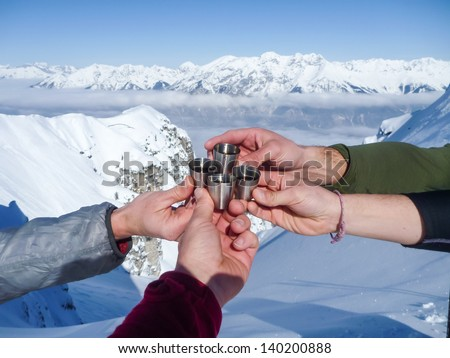 Celebration in mountains.  Shots of spirits at the top of mountain summit during ski tour in the Alps.   - stock photo