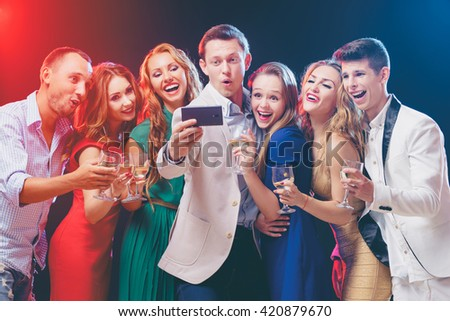 Celebration, party and technology. Group of seven happy smiling friends taking selfie together by smartphone.