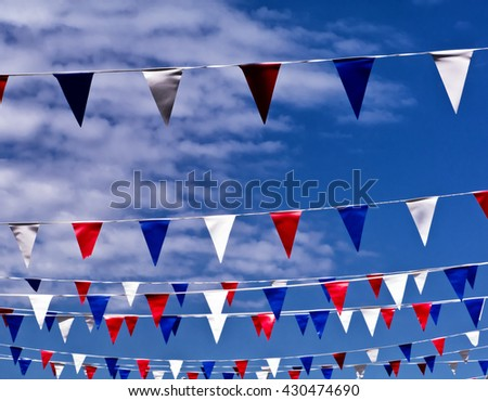 Celebration pennants against spring sky; colored bunting flying against spring or summer sky  - stock photo
