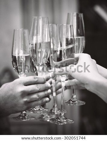 Celebration. People holding glasses of champagne making a toast. DOF. Natural light. Photo in motion. Black and white image - stock photo