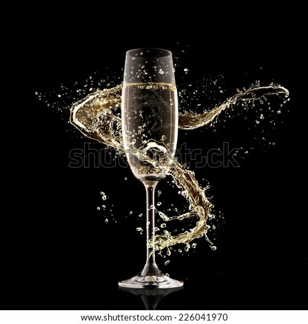 Celebration theme. Glass of champagne with splash, isolated on black background - stock photo
