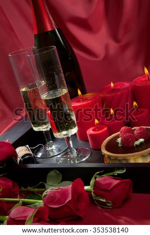 Celebration tray for Valentines Day - Champagne, chocolate raspberry cake, candles, and red roses. - stock photo