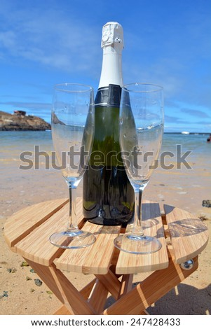 Celebration with two glasses of champagne on the beach in paradise island