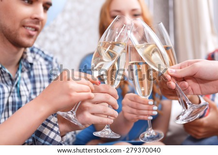 Celebration. Young people clinking glasses of champagne celebrating birthday of their friend selective focus