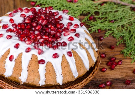 Celebratory cake decorated with  pomegranate and sugar icing on a wooden background - stock photo