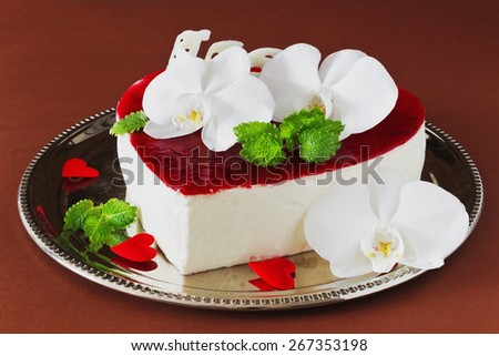 celebratory cake in the form of heart with orchid flowers on a brown background. valentine's day, mother's day - stock photo