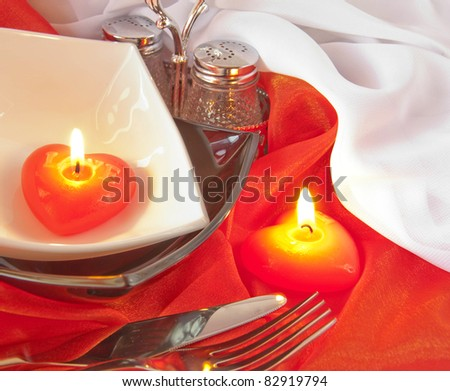 Celebratory table layout with red napkins and candles in the form of heart - stock photo