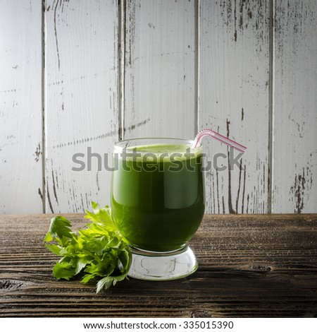 Celery juice on wooden table - stock photo
