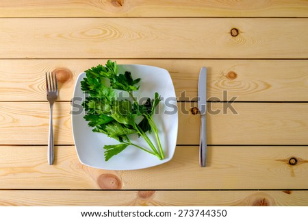 Celery on white plate with knife and fork on wooden background. Diet concept. - stock photo