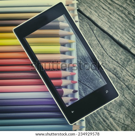 Cell phone  and crayons on wooden table background  - stock photo