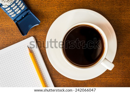 Cell phone and cup of the coffee on the wooden table with a notebook and a pencil