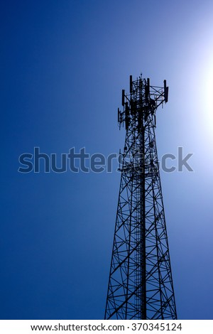 Cell phone antenna tower with the blue sky and rays