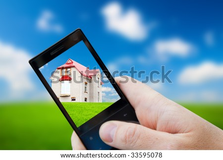 cell phone in hand and house - stock photo