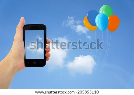 Cell phone in hand take photo of beautiful balloon and sky view - stock photo