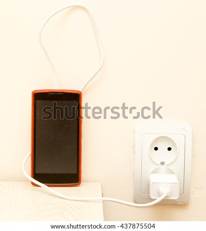cell phone is being charged from the electrical outlet - stock photo