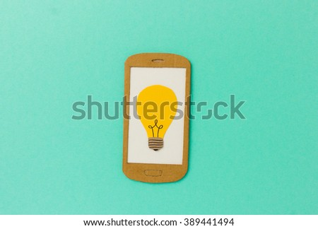 Cell phone paper model with light bulb symbol - image concept for e-learning, online classes, research tools - stock photo