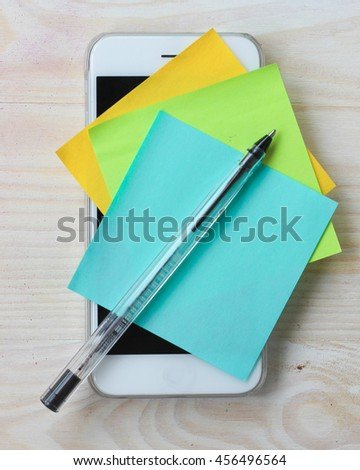 Cell phone reminder notes. Paper sticky notes and black pen on smart phone. - stock photo