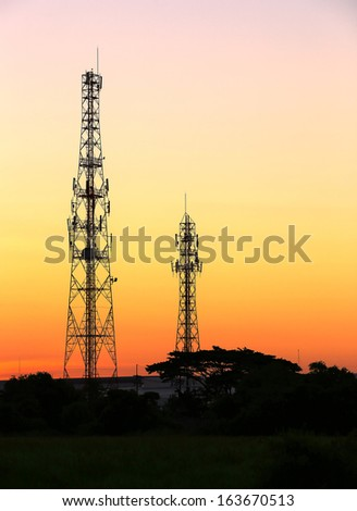 Cell phone tower and radio antenna at sunrise