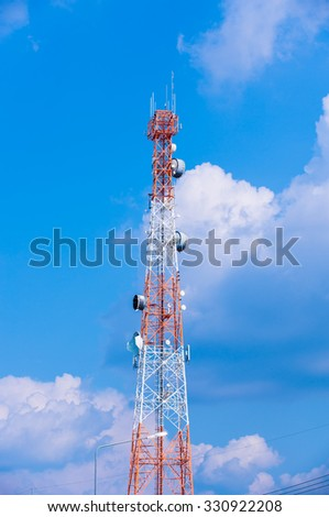 Cell phone tower rises against a blue sky