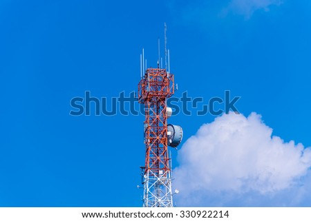 Cell phone tower rises against a blue sky - stock photo