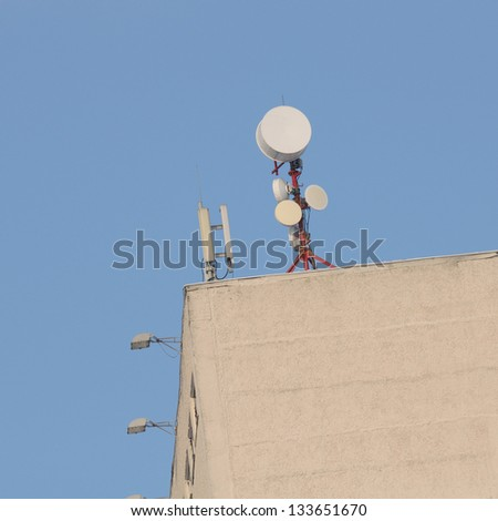 Cell Phone Towers on Roof Against Blue Sky - stock photo