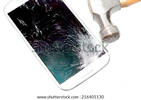 Cell phone with a broken screen due to a hammer hit - stock photo