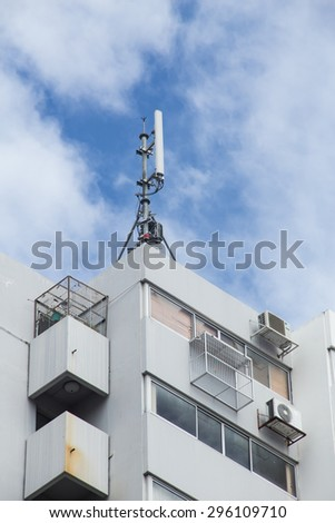 Cell site, Telecommunications radio tower or mobile phone base station on top of apartment or condominiumin - stock photo