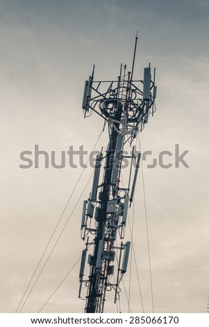 Cell site, Telecommunications radio tower or mobile phone base station with atop the antennas, vintage color tone. - stock photo