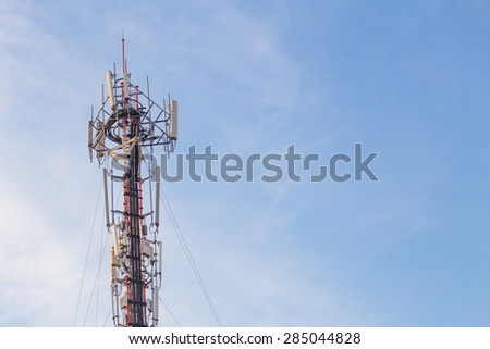 Cell site, Telecommunications radio tower or mobile phone base station with atop the antennas with Blue Sky and cloud background. - stock photo