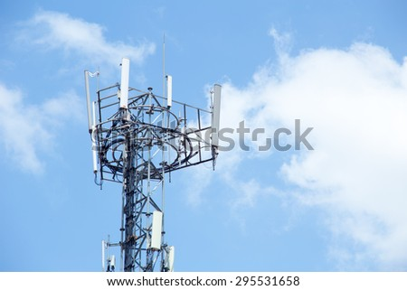 Cell site, Telecommunications radio tower or mobile phone base station with cloud and blue sky background - stock photo