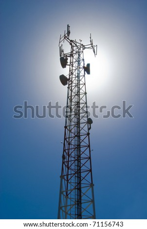 Cell tower and radio antenna back lit by sun - stock photo