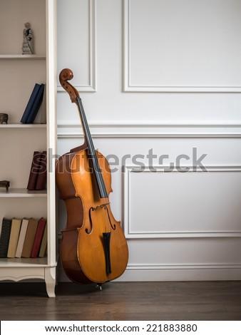 Cello in classical interior near bookshelf - stock photo