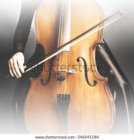 Cello player cellist playing music instrument hands closeup. Orchestra instruments