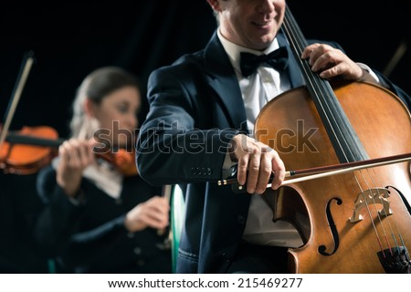 Cello professional player with symphony orchestra performing in concert on background.
