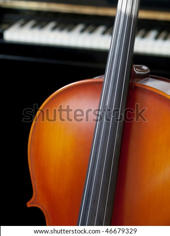 Cello standing in front on a piano - stock photo