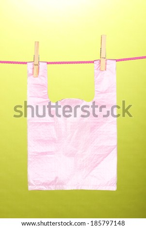Cellophane bag hanging on rope on green background - stock photo