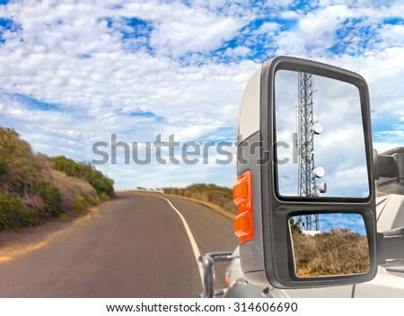 Cellphone communication tower reflection in truck side rear view mirror. On the road motion blur, rural area, blue sky with clouds background. Wireless connection to the internet anywhere concept.   - stock photo