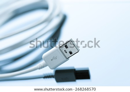 Cellphone usb cable charging cord on a blue reflective surface - stock photo